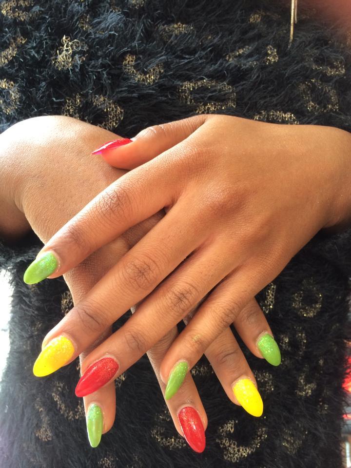 Kunstnagels met vrolijke kleuren nagellak. Geel, rood en groen.