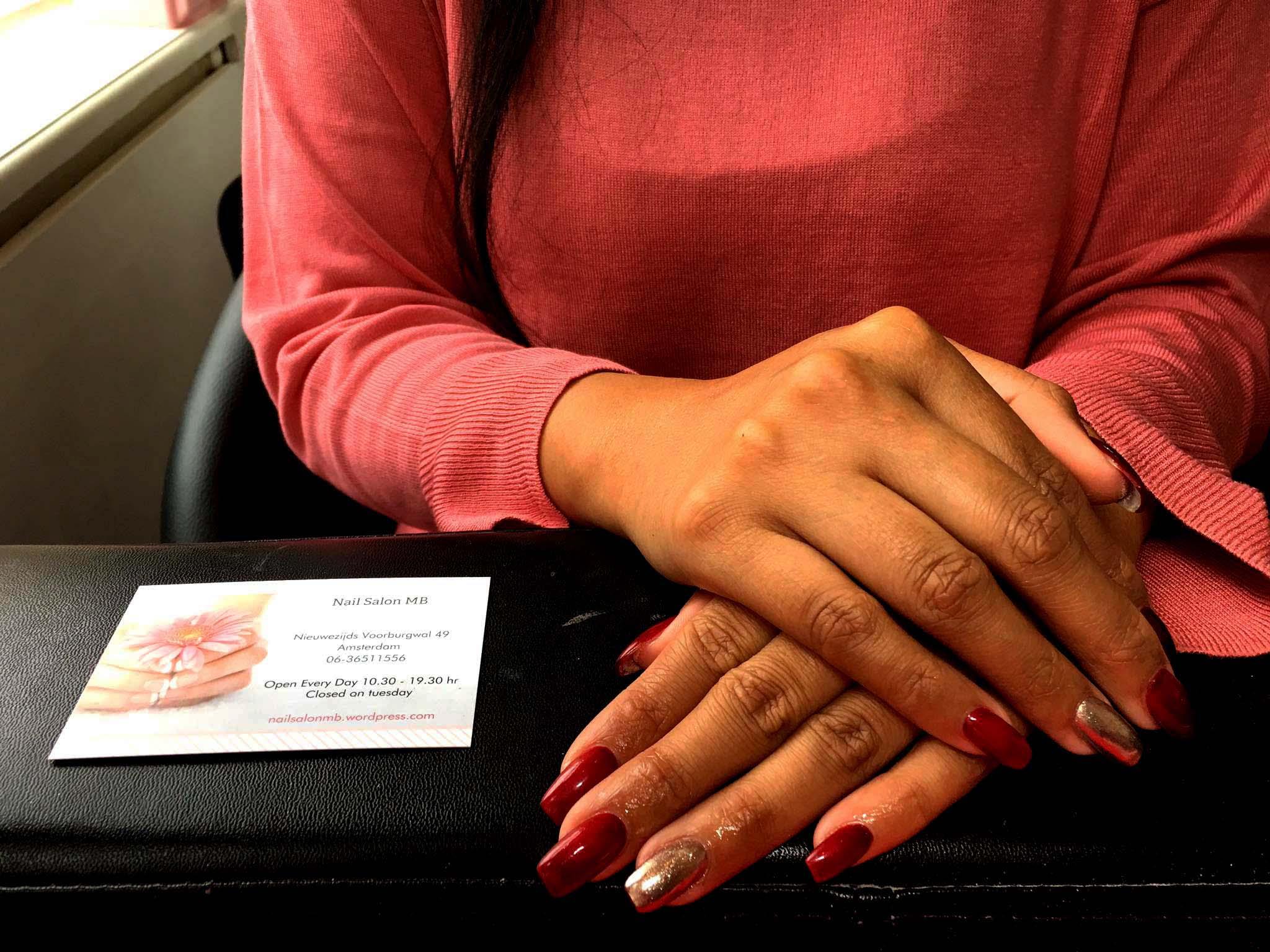 Donkerrode kunstnagels met als nagelvorm squoval met gouden ringvingers